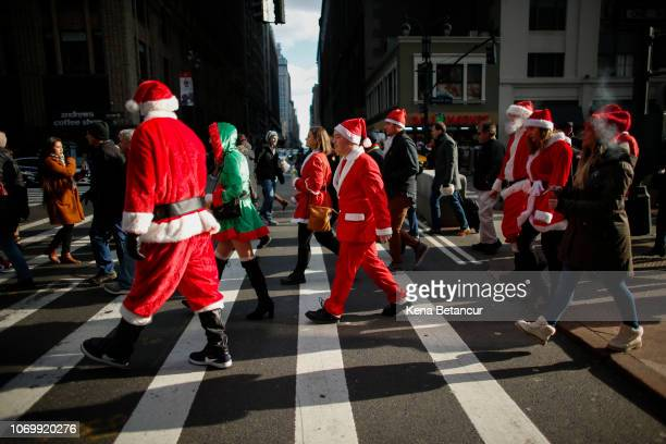 People in costume walk as they take part during the annual New York SantaCon bar crawl on December 8 2018 in New York City SantaCon is in it's 20th...