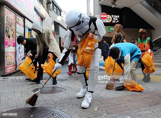 People in costumes collect garbage on the street after their Halloween party at Tokyo's Shibuya fashion district on November 1, 2015. Hundreds of...