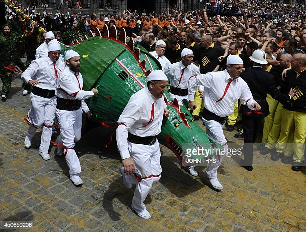 People in costumes take part in a performance showing the fight between a Saint and the dragon at Ducasse during the Doudou folkloric festival in...