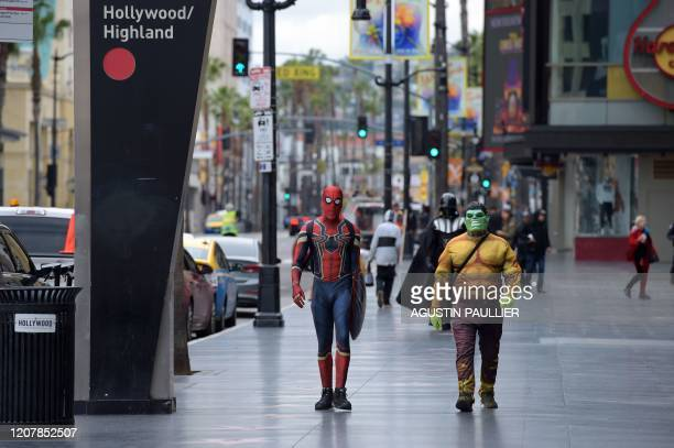 People in costumes walk along Hollywood Boulevard in Hollywood on March 20 a day after Los Angeles County announced a near-lockdown, urging all...