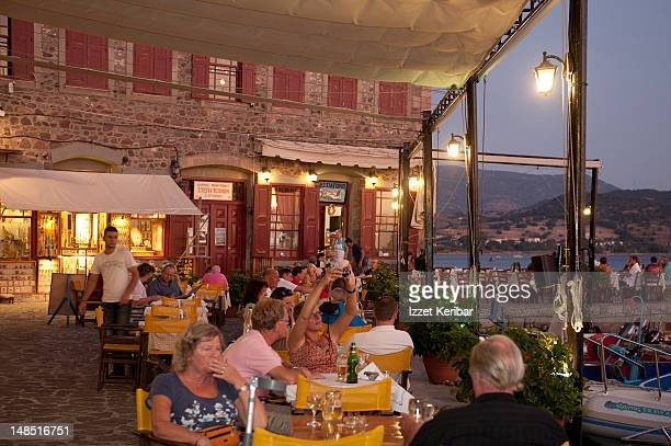 People in courtyard of restaurant in Molyvos port at dusk.