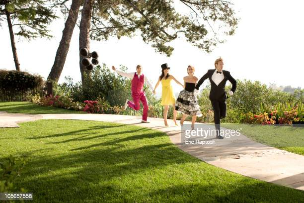 People in elegant clothing running on path in park