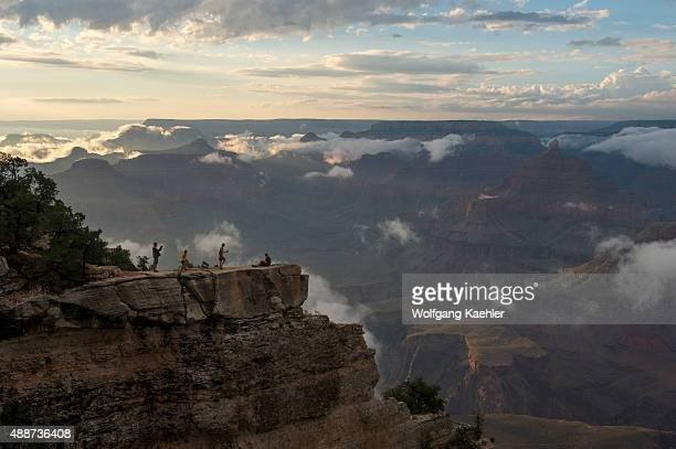 People in evening light on a rock outcrop near Mather Point on the South Rim of the Grand Canyon with clouds clearing after a thunderstorm in the...