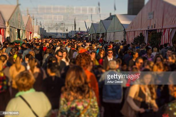 People in Feria de Abril in Barcelona at sunset.