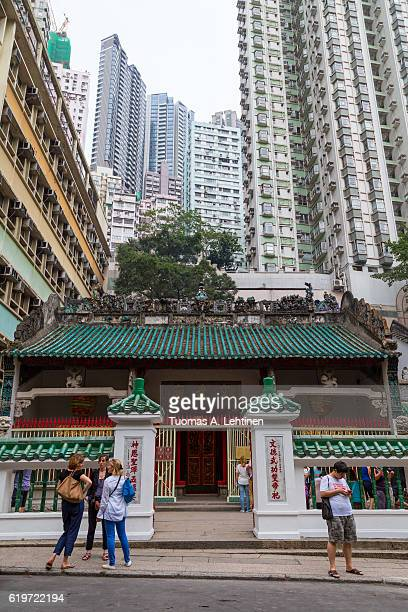 people in front of the man mo temple in sheung wan, hong kong, china. high-rise residential skyscrapers are behind it. - man motempel stockfoto's en -beelden
