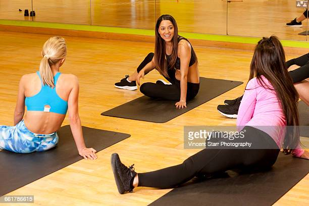 People in gym sitting on yoga mats chatting