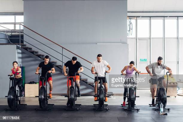 people in gym using exercise bikes - peloton stock pictures, royalty-free photos & images