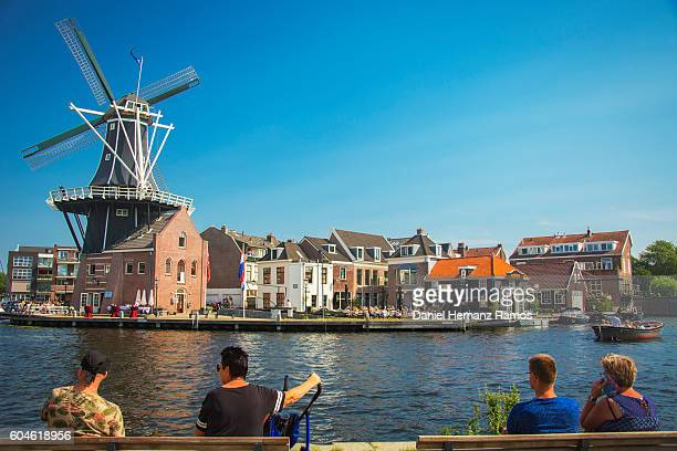people in Haarlem watching its famous traditional windmill in a canal, Netherlands