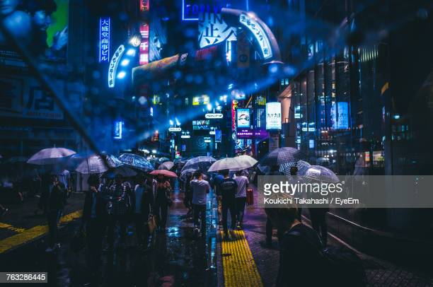 people in illuminated city at night - city photos stock pictures, royalty-free photos & images