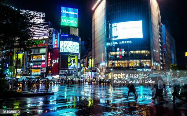 People In Illuminated City During Monsoon At Night