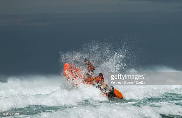 People In Lifeboat On Sea With Splashing Wave