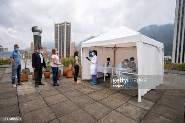 people in line waiting to get their covid-19 vaccine at a stand - lining up stock pictures, royalty-free photos & images