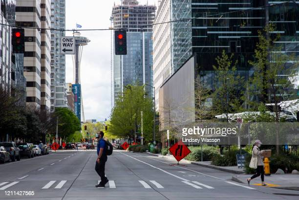 People in masks cross the street, the Space Needle in the background, next to the downtown Amazon campus on April 30, 2020 in Seattle, Washington....