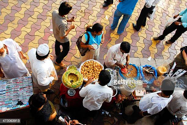 people in mumbai buying snacks on street market - chicken tikka stock photos and pictures