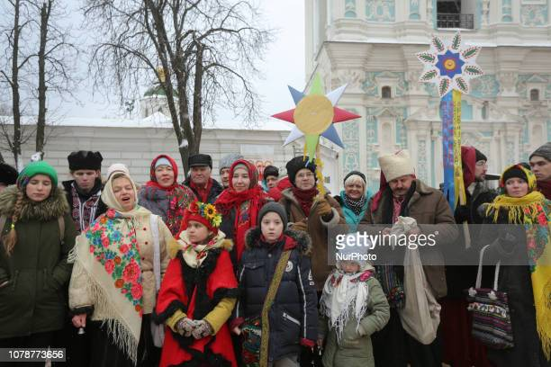 People in national costumes sing carols as they stand in a line to look at a Tomos document signed by Ecumenical Patriarch Bartholomew which...