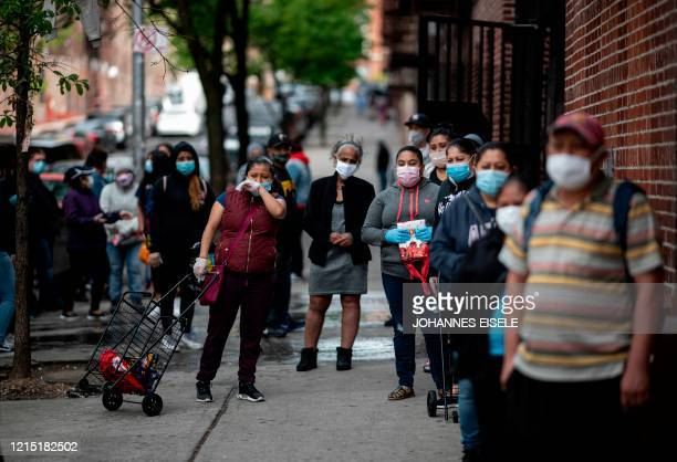 People in need and from the community line up for food donations on May 19, 2020 in the Bronx borough of New York City. - A church in New York city...
