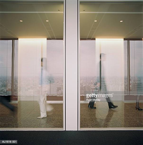 People in office hallway, seen through glass, reflecting city