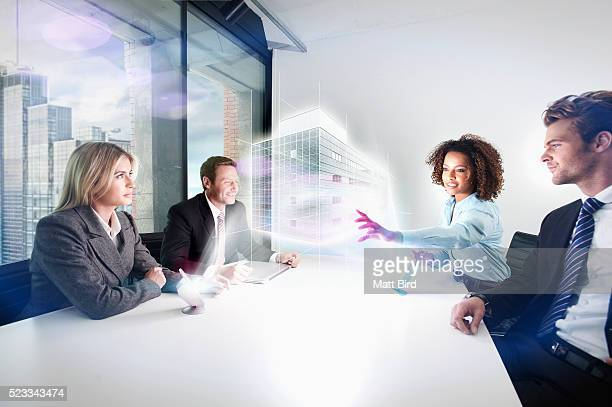 People in office meeting looking at 3d projection from futuristic device