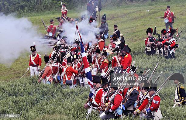 People in period British infantry uniforms reenact the 1815 Battle of Waterloo between the French army led by Napoleon and the Allied armies led by...