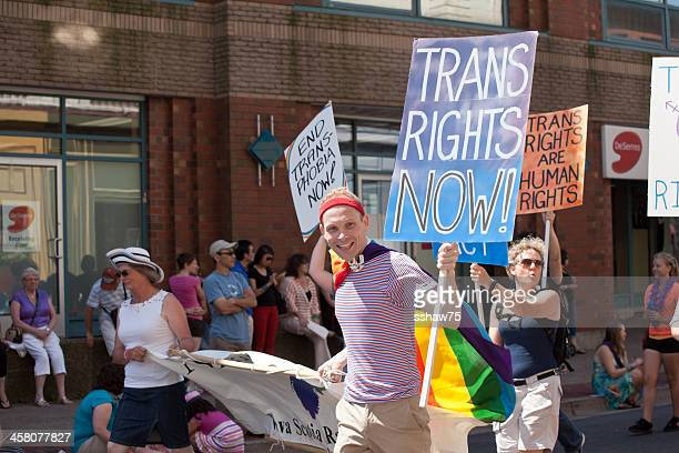 people in pride parade carrying protest signs - flag of nova scotia stock pictures, royalty-free photos & images