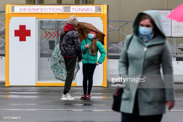 People in protective masks near Desinfection tunnel installed in the center of Kyiv, amid the coronavirus disease COVID-19 outbreak in Kyiv, Ukraine...