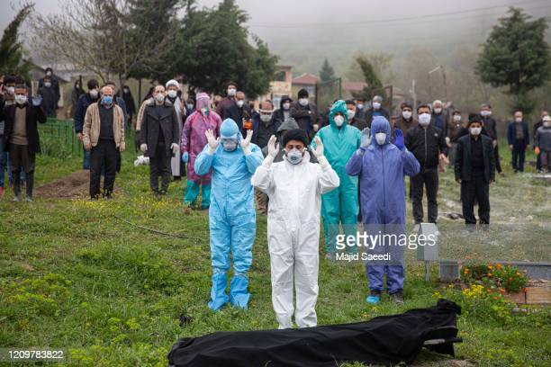 People in protective outfits pray at the body of a COVID-19 victim ahead of burying him as friends and family watch from further away on April 10,...