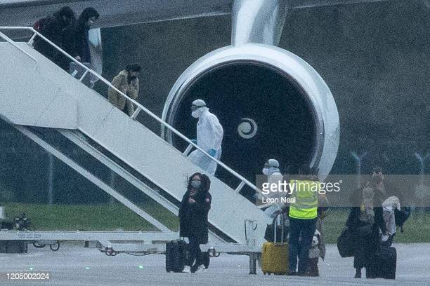 People in protective suits assist passengers as they disembark from a plane carrying 150 Britons who were trapped in Wuhan following a Coronavirus...