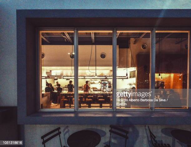 people in restaurant seen through window - photographed through window stock pictures, royalty-free photos & images