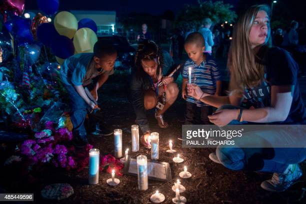 People in Roanoke participate in a candlelight vigil placing their candles near the memorial shrine of balloons and flowers on the front driveway of...