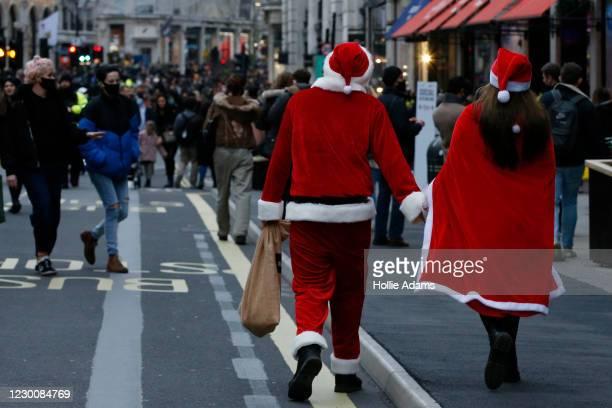 People in Santa costumes walk amongst Christmas shoppers Regent Street on December 12, 2020 in London, England.