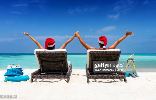 people in santa hat sitting on lounge chair at beach against sky - caribbean christmas stock pictures, royalty-free photos & images
