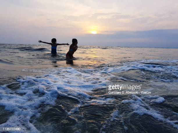 people in sea against sky during sunset - gabon stock pictures, royalty-free photos & images