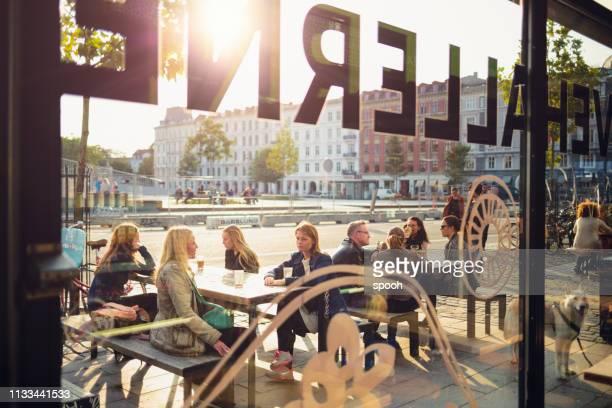 mensen in sidewalk cafe in copehnagen. - café bar gebouw stockfoto's en -beelden