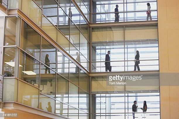 people in silhouette on multiple levels of corridor through glass - distant stock pictures, royalty-free photos & images
