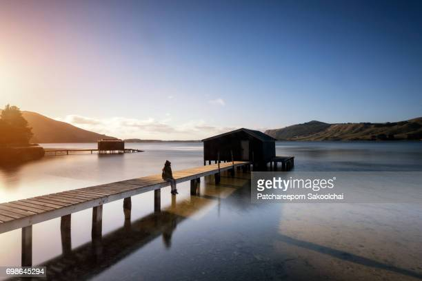 people in silhouette sitting on house over the water - otago region stock pictures, royalty-free photos & images