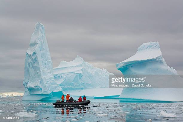 People in small inflatable zodiac rib boats passing towering sculpted icebergs on the calm water around small islands of the Antarctic Peninsula.