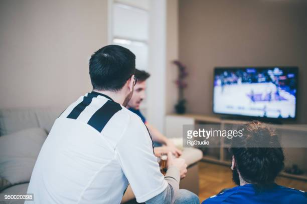 people in sport jerseys watching tv at home - match sport stock pictures, royalty-free photos & images