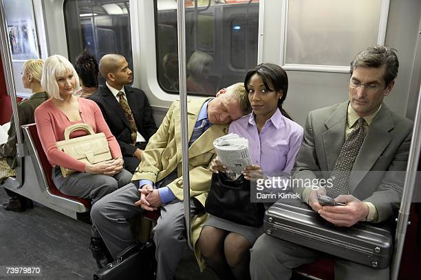people in subway train, man resting head on woman's shoulder - underground stock photos and pictures