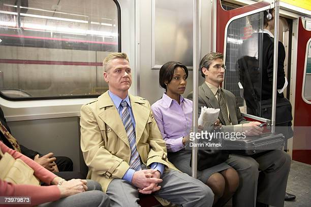 People in subway train, sitting side by side