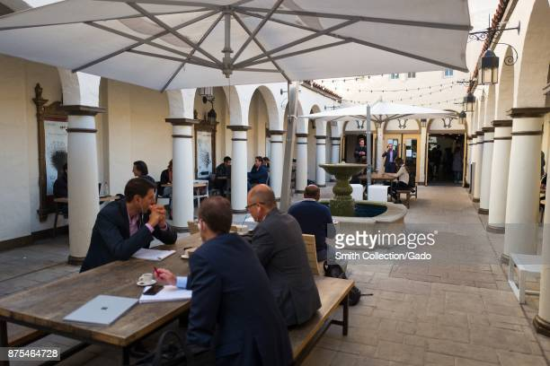 People in suits dine and meet outdoors at the Blue Bottle Coffee shop in Silicon Valley Palo Alto California part of an adaptive reuse which turned...