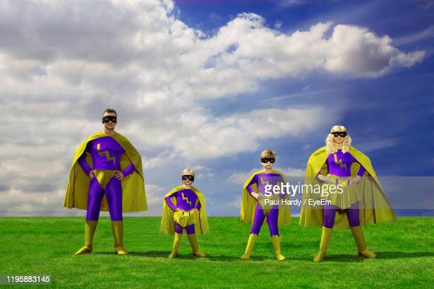 people in superhero costumes standing on grass against sky - cape stock pictures, royalty-free photos & images