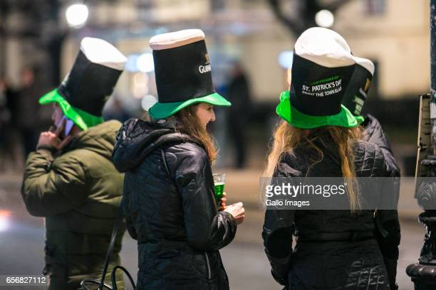 People in symbolic hats in front of the Molly Malone's Irish Pub seen during Saint Patricks Day celebration on March 17, 2017 in Warsaw, Poland....