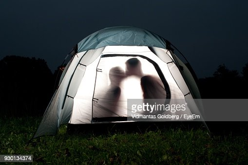 People In Tent On Field At Night