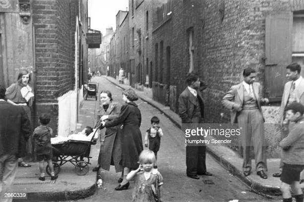 People in the area of narrow streets around Whitechapel High Street east London Original Publication Picture Post 27 Whitechapel pub 1938