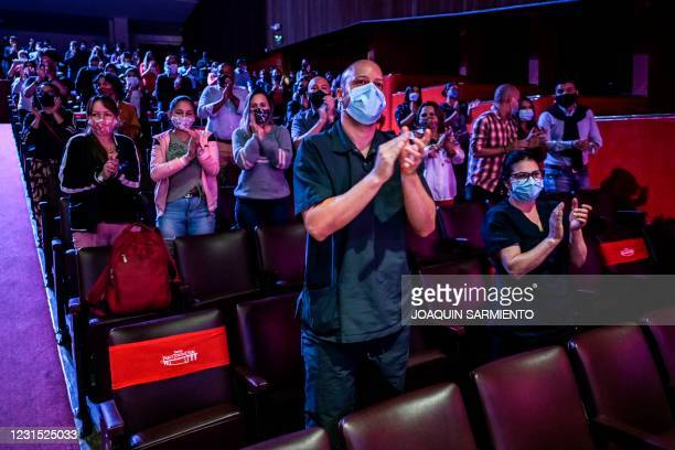 People in the audience applaud during a concert by the Medellin Philharmonic Orchestra at the Pablo Tobon Uribe Theater, as theaters reopen, amid the...