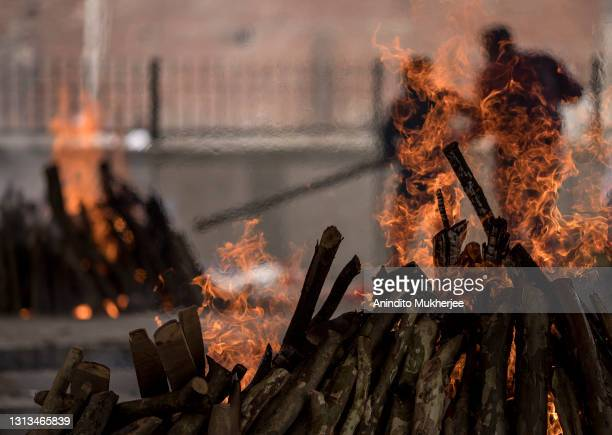 People in the background perform the last rites of their relative who died of the Covid-19 coronavirus disease during a mass cremation at a...
