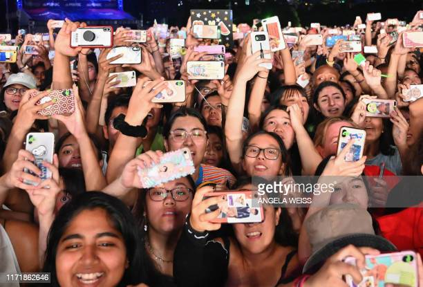 TOPSHOT People in the crowd hold up their smartphones during the 2019 Global Citizen Festival Power The Movement in Central Park in New York on...