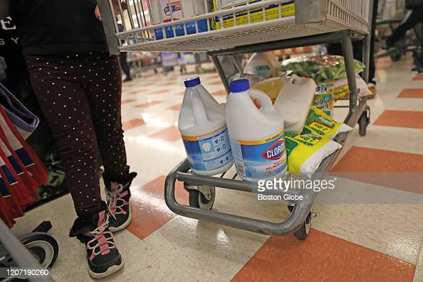People in the long lines at Market Basket in Waltham, MA buy bleach and frozen peas, among other items, as they prepare for possible quarantine due...