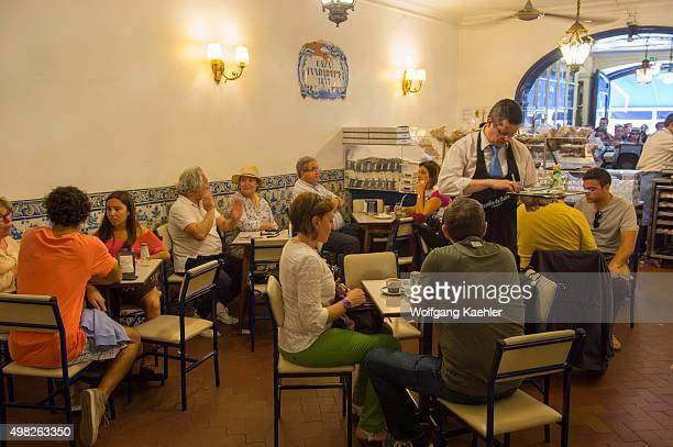 People in the Pasteis de Belem bakery and store having Pastel de nata which is a Portuguese egg tart pastry in Lisbon the capital city of Portugal
