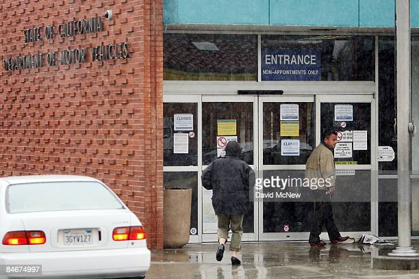 People in the rain approach the entrance to the State of California Department of Motor Vehicles February 6 2009 in Pasadena California The DMV is...